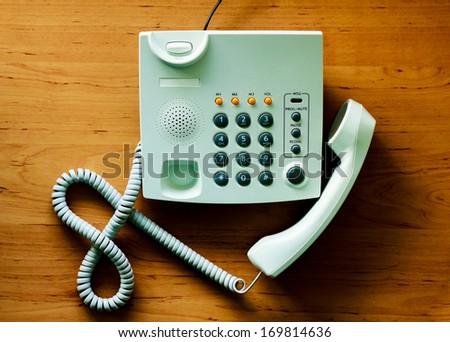 modern white telephone on the wooden desk  - stock photo