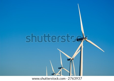 Modern white wind turbines or wind mills producing energy to power a city