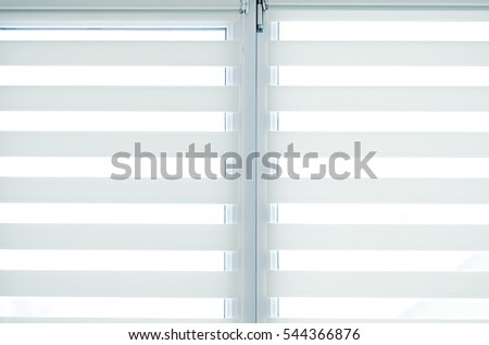 Modern wide white horizontal blinds on a window. Daylight