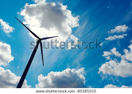 Modern wind energy turbine power station under blue sunny sky with many clouds - stock photo
