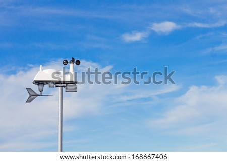 Modern wind speed and direction indicator. Wind vane, or weathervane, to show direction, and electronic anemometer with rotating cups to measure velocity. Blue sky and clouds background. Room for text