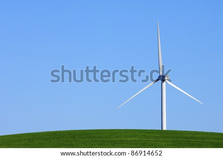 Modern windmill with blue sky in a green meadow - stock photo