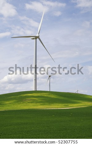modern windmills in a green meadow with cloudy sky - stock photo