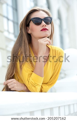 Modern woman in sunglasses in urban backgrounds - stock photo