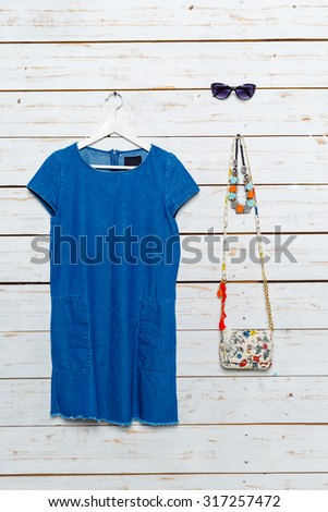 Modern woman's clothes on white wooden background - stock photo