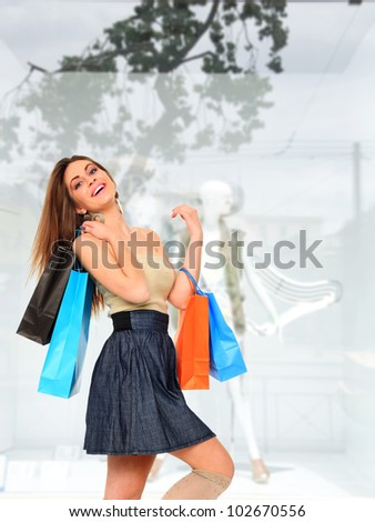 Modern woman shopping in mall holding bags - stock photo