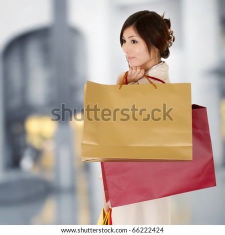 Modern woman shopping in mall holding bags and thinking. - stock photo