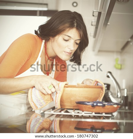modern woman taken the food out of the kitchen oven - stock photo