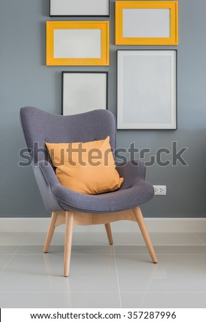 modern wooden chair with orange pillow and picture frame on wall - stock photo