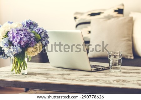 Modern wooden coffee table, laptop and cozy sofa with pillows. Living room interior and home decor concept. Toned image - stock photo
