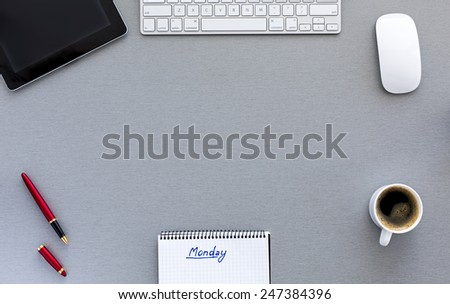 Modern working place on Monday morning. From above view on well equipped working place with tablet PC, computer mouse and keyboard, red pen, cup of fresh coffee, notepad with handwritten sign MONDAY - stock photo