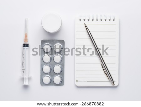 Modern workplace with a note, pen, pills and syringes. Medicine concept. View from above - stock photo