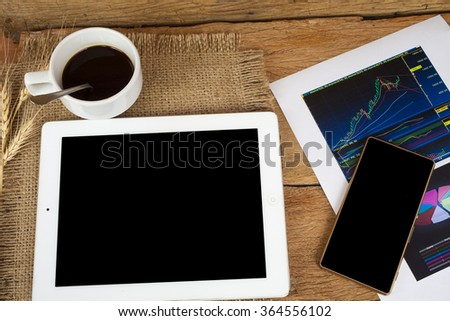 Modern workplace with digital tablet computer , graph paper and mobile phone