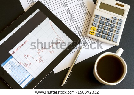 Modern workplace with digital tablet showing charts and diagram on screen, coffee, pen and paper with numbers. - stock photo