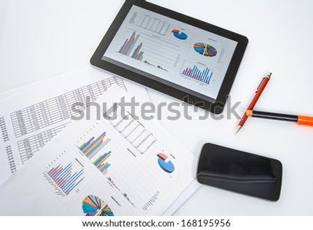 Modern workplace with digital tablet, smartphone and chart documents - stock photo
