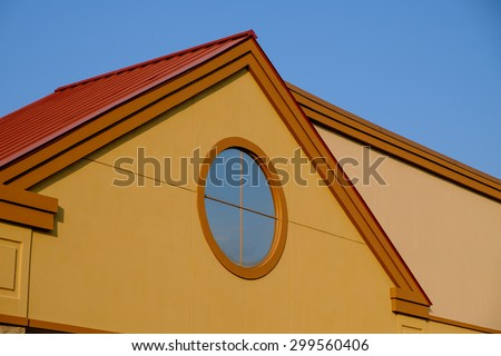 Modern Yellow building with red roof at sunset - stock photo