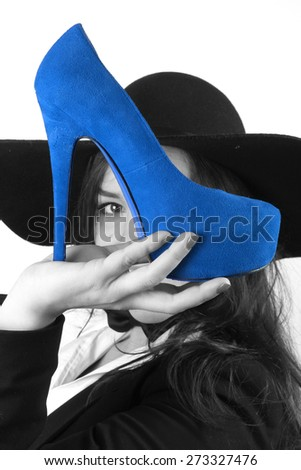 modern young brunette girl with beautiful eyes holding blue female shoes with a high heel and a black hat retro looks - stock photo