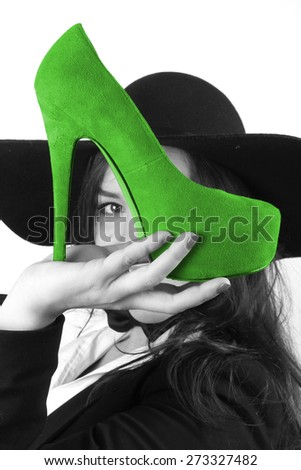 modern young brunette girl with beautiful eyes holding green female shoes with a high heel and a black hat retro looks - stock photo