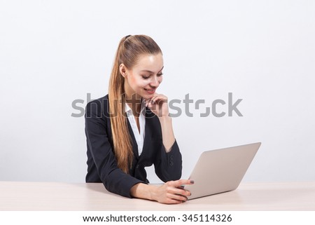 modern young business woman in a business suit on a white background minimalist office sits at a table in front of a laptop.