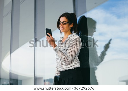 Modern young business woman or entrepreneur texting on her smartphone. Stylish professional sending message form her cellphone. - stock photo