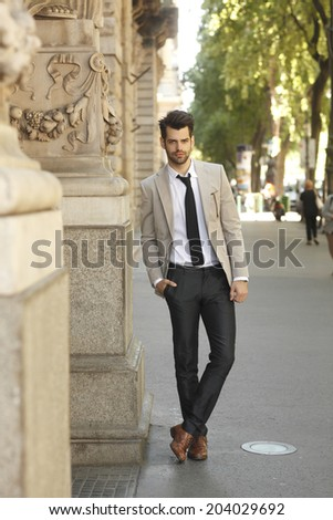 Modern young businessman standing in front of business center.