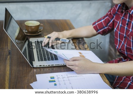 Modern young employee analyzing financial data in office,businessman sitting in front of net book in office,analyzing financial chart,writing business plan ,working on his laptop in a coffee shop - stock photo