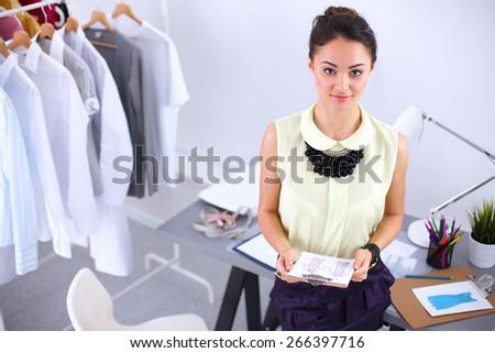 Modern young fashion designer working at studio - stock photo