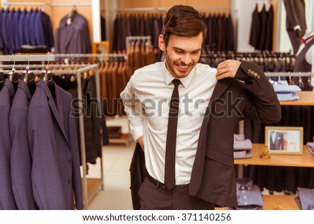 Modern young handsome businessman smiling and trying on classical suit in the suit shop - stock photo