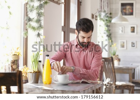 Modern young man sitting at desk and drinking tea at coffee shop. - stock photo