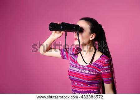 Modern young woman with binoculars in hand. Watching through binocular. Space for text.  pink background  - stock photo