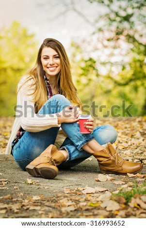 Modern young woman with takeaway coffee outdoors in autumn. Fashionable happy blonde teenage girl in casual autumn outfit sitting in park. Vertical, retouched, vibrant colors. - stock photo