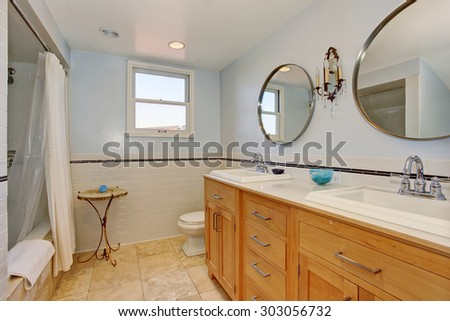 Modernized bathroom with two oval mirrors, two sinks, and a white shower curtain.