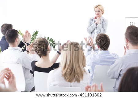Modest young pretty woman standing surprised in the front of her work colleagues during meeting. Friendly businesspeople applauding for a woman