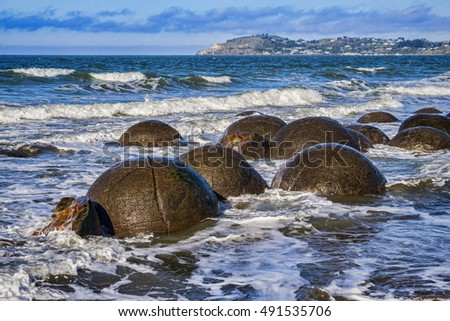 Moeraki Boulders, Otago, New Zealand, on a fine spring day at high tide.