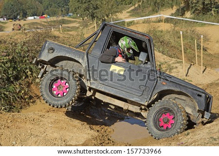"MOHELNICE, CZECH REPUBLIC - OCT 05. Off-road car is owercoming a terrain  on a trial race in the ""BIG SHOCK CUP Trial 2013"" on October 05, 2013 in Mohelnice, Czech Republic. - stock photo"
