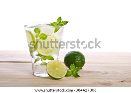Mohito mojito drink with ice mint and lime on wooden table - stock photo