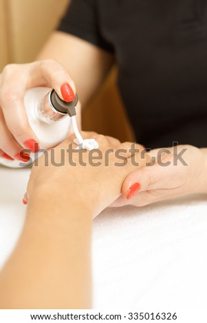 Moisture your skin. Close up shot of beautician applying cream on client hand - stock photo