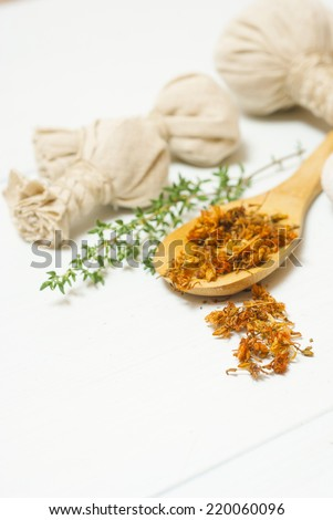 moisturizer with dried St. John's Wort on wooden spoon and floating flowers - stock photo