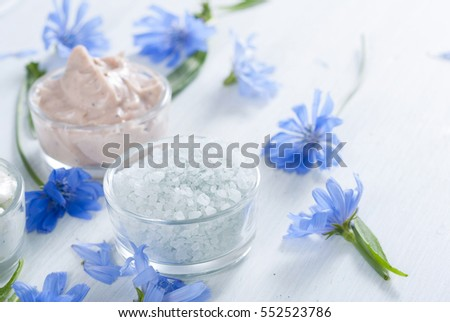 moisturizers, bath salts and powder compacts with blue chicory flowers on white wood table