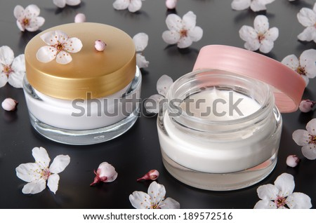 Moisturizing cream with flowers, on grey background