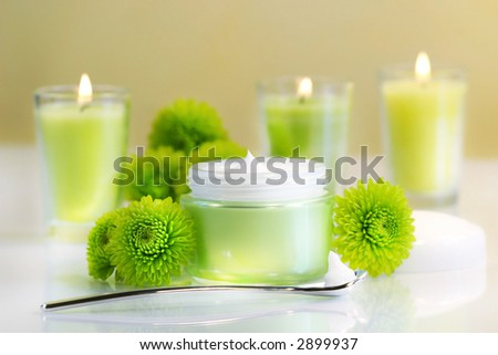 Moisturizing face cream with candles - stock photo