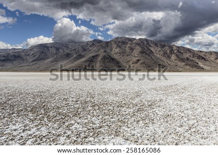 Mojave desert dry lake salt flat with dark storm clouds. - stock photo