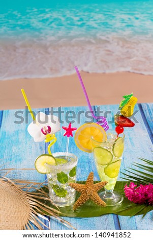 Mojito and lemon lime Cocktails in tropical blue wood at turquoise Caribbean beach - stock photo
