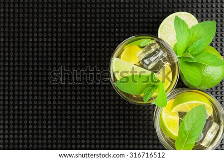 Mojito cocktail and ingredients over black rubber mat. Top view with copy space - stock photo