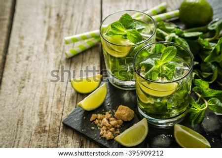 Mojito cocktail and ingredients, rustic wood background, copy space - stock photo