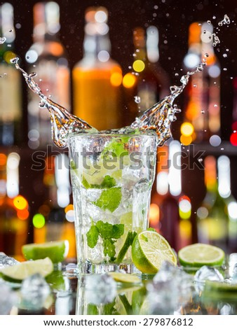 Mojito cocktail drink with splash, served on bar counter with blur bottles on background - stock photo