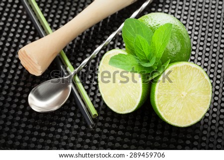 Mojito cocktail ingredients and utensils on black rubber mat - stock photo