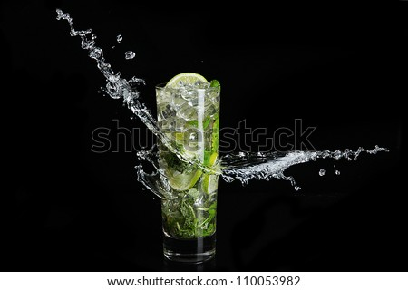 Mojito cocktail on black background with splash - stock photo