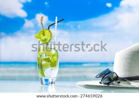 Mojito cocktail with fresh lime at the beach - stock photo