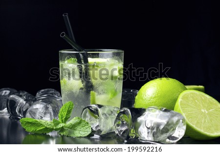 Mojito cocktail with fresh limes, mint and ice cubes on black table - stock photo